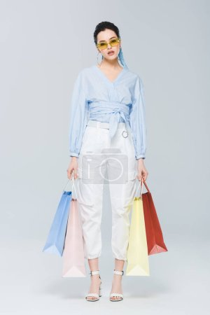 Photo pour Belle fille à la mode avec des sacs à provisions regardant l'appareil-photo sur le gris - image libre de droit