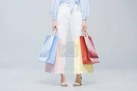 Foto de Vista recortada de la chica de moda con bolsas de compras en gris - Imagen libre de derechos