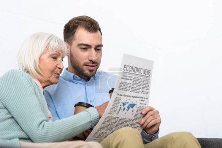 Photo pour Homme et mère aînée lisant journal à la maison - image libre de droit