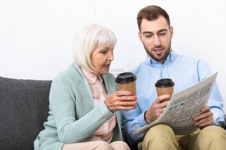 Photo pour L'homme et la mère aînée retenant des tasses de café et journal de lecture à la maison - image libre de droit