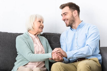 Photo for Smiling senior mother and son holding hands and looking at each other while sitting on sofa - Royalty Free Image