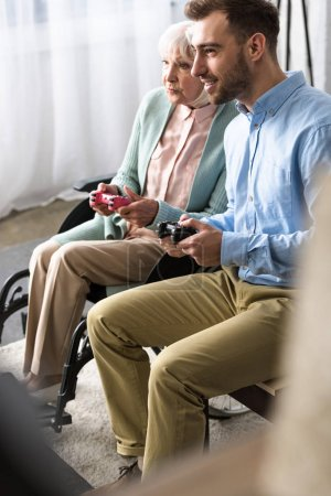 Photo for KYIV, UKRAINE - APRIL 15, 2019: disabled senior woman with son playing video game with joysticks - Royalty Free Image