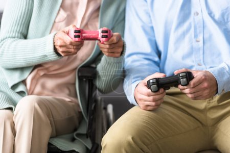 Photo for KYIV, UKRAINE - APRIL 15, 2019: cropped shot of senior woman with adult son playing video game - Royalty Free Image