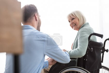 Photo for Back view of man near disabled senior mother at home - Royalty Free Image