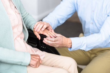 Photo for Partial view of man holding hands with disabled senior mother on wheelchair - Royalty Free Image