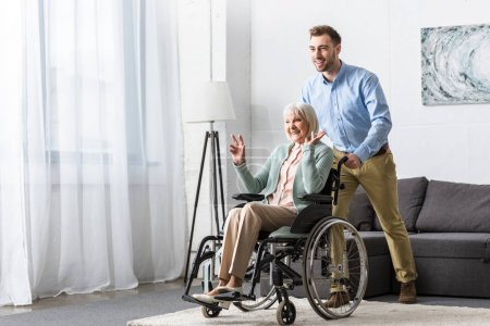 Photo for Smiling man carrying disabled senior mother on wheelchair - Royalty Free Image