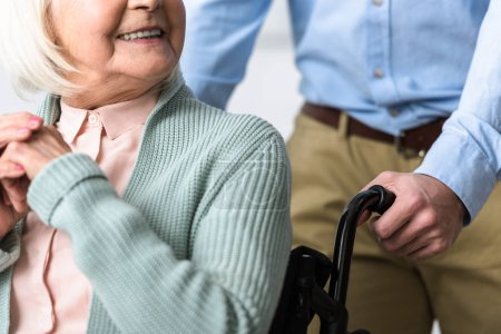 Photo for Cropped view of man carrying disabled senior mother on wheelchair - Royalty Free Image