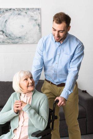 Photo pour Homme de sourire portant la mère aînée handicapée sur le fauteuil roulant - image libre de droit