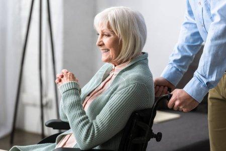 Photo pour Vue recadrée de l'homme portant une mère aînée handicapée en fauteuil roulant - image libre de droit