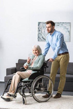 Photo pour Vue pleine longueur d'un homme souriant portant une mère aînée handicapée en fauteuil roulant - image libre de droit