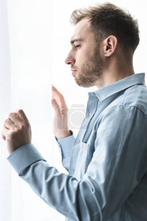Photo for Side view of sad bearded man in blue shirt looking away at home - Royalty Free Image
