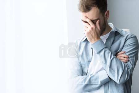 Photo for Depressed man in blue shirt covering face with hand on at home - Royalty Free Image