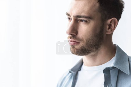 Photo for Sad man in blue shirt looking away at home - Royalty Free Image