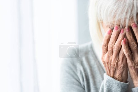 Photo for Partial view of crying senior woman covering face with hands - Royalty Free Image