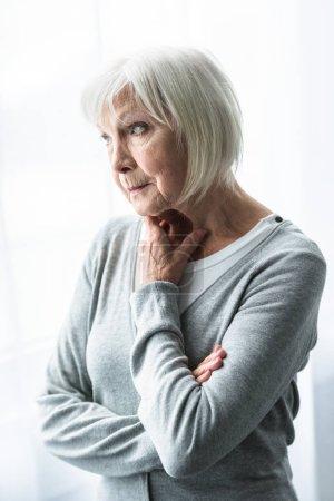 Photo for Pensive senior woman in grey cardigan looking away - Royalty Free Image
