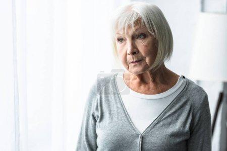 Photo pour Femme aînée pensive dans le cardigan gris regardant loin - image libre de droit
