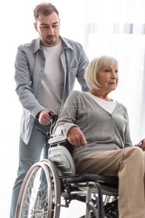 Photo pour Homme barbu portant la mère handicapée sur le fauteuil roulant à la maison - image libre de droit