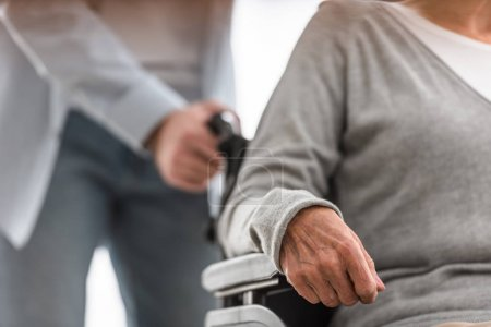 Photo pour Vue recadrée de l'homme portant la mère handicapée sur le fauteuil roulant à la maison - image libre de droit