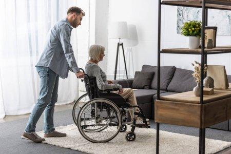 Photo pour Vue pleine longueur de l'homme portant la mère handicapée sur le fauteuil roulant - image libre de droit