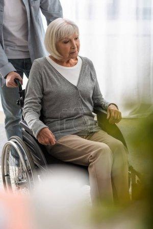 Photo pour Vue recadrée de l'homme portant la mère handicapée sur le fauteuil roulant - image libre de droit