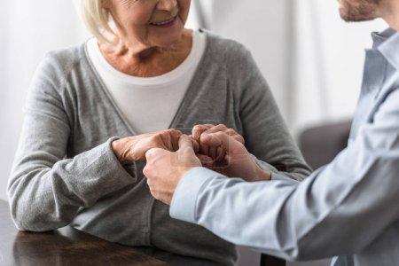 Photo pour Vue recadrée de femme aînée de sourire retenant des mains avec le fils - image libre de droit