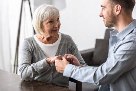 Photo pour Homme de sourire retenant des mains avec la mère aînée une maison - image libre de droit