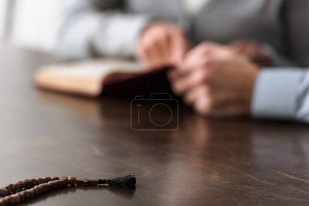 Photo pour Foyer sélectif de deux personnes et chapelet en bois au premier plan - image libre de droit