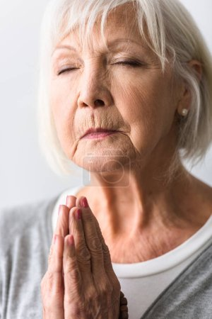 Photo for Senior woman showing please gesture and praying with closed eyes - Royalty Free Image