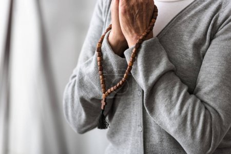 Photo for Partial view of senior woman praying with wooden rosary - Royalty Free Image