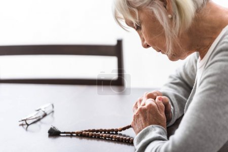 Foto de Senior woman holding wooden rosary and praying with closed eyes - Imagen libre de derechos