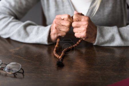 Photo for Partial view of senior woman holding wooden rosary - Royalty Free Image