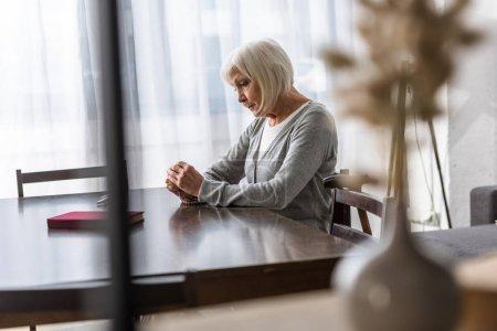 Photo pour Femme aînée pensive s'asseyant à la table et retenant le chapelet - image libre de droit