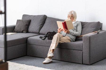 Photo pour Femme aînée dans des glaces s'asseyant sur le sofa et le livre de lecture dans le salon - image libre de droit