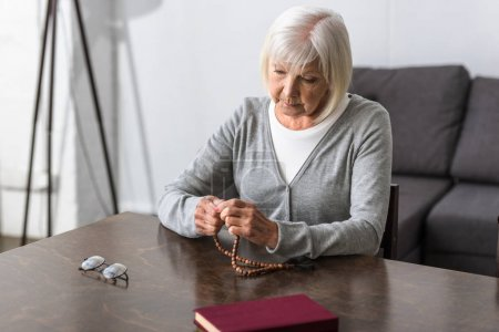 Photo for Pensive senior woman sitting at table and holding rosary - Royalty Free Image