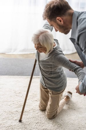 cropped view of man helping sick senior mother with cane