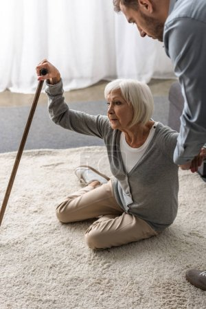 Photo pour Vue recadrée de l'homme aidant la mère aînée malade avec la canne - image libre de droit