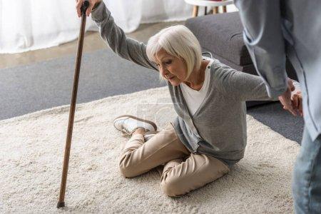 Photo pour Vue recadrée de l'homme aidant la mère aînée malade avec la canne tombée sur l'étage - image libre de droit