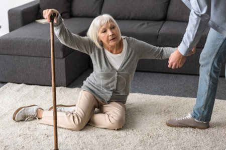 Photo pour Cropped view of man helping sick senior mother with cane fallen on floor - image libre de droit
