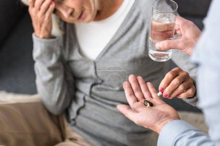Photo pour Vue partielle de l'homme donnant au verre aîné de mère de l'eau et de la médecine - image libre de droit