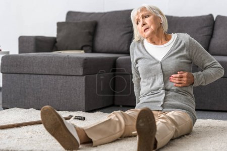 Photo for Suffering senior woman with heart attack sitting on carpet - Royalty Free Image