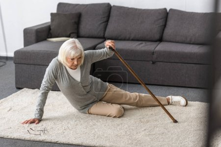 Photo for Suffering senior woman with heart attack on carpet - Royalty Free Image