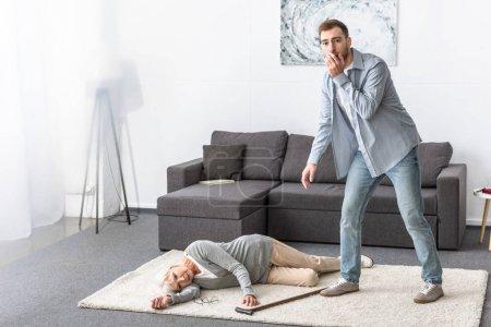 Photo pour Vue pleine longueur de l'homme inquiété restant près de la femme aînée se trouvant sur le tapis - image libre de droit