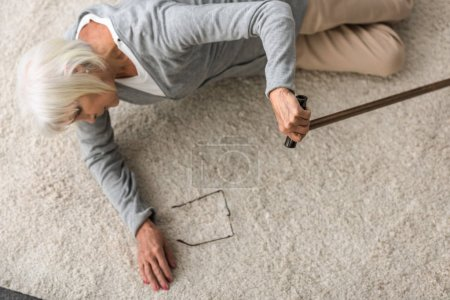 Photo for Overhead view of sick senior woman with walking stick lying on carpet - Royalty Free Image