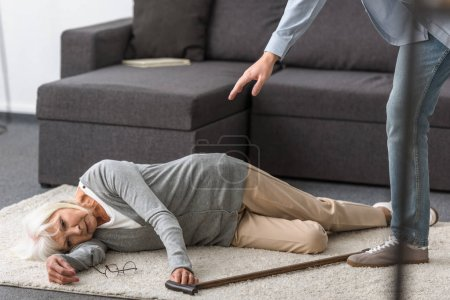 Photo for Partial view of man near senior woman with walking stick lying on carpet - Royalty Free Image