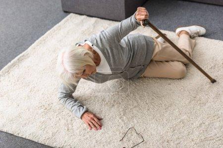 Photo pour Vue aérienne de la femme aînée malade avec le bâton de marche se trouvant sur le tapis - image libre de droit