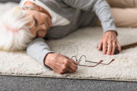 Photo pour Femme aînée malade avec des glaces se trouvant sur le tapis - image libre de droit