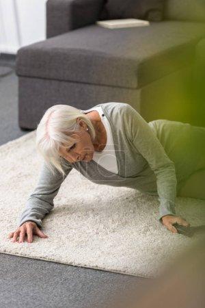 Photo pour Femme aînée malade avec la canne se trouvant sur le tapis - image libre de droit