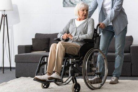 Photo pour Vue recadrée de l'homme portant la mère aînée sur le fauteuil roulant - image libre de droit