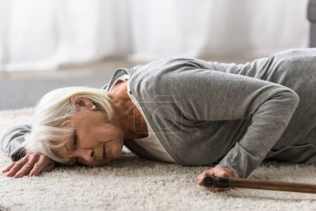 Photo for Ill senior woman with cane lying on carpet with closed eyes - Royalty Free Image