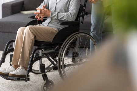 Photo for Cropped view of man carrying senior mother on wheelchair - Royalty Free Image